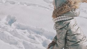 Mother playing snow with daughter in slow motion. Family have fun in winter day stock footage