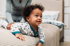 Mother playing with son on a bed. royalty free stock photography