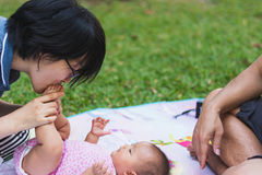 Mother playing and taking care of  baby at park Stock Photos