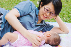 Mother playing and taking care of  baby at park Stock Photography