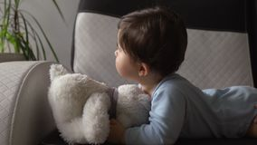Mother playing with teddy bear and her baby son indoor flat - Asian mixed ethnicity child Boy wearing blue body shirt. With smiling bear cartoon - Caucasian mom stock video