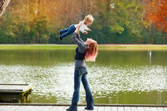 Mother playing throwing up baby girl in a lake Stock Photos
