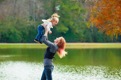 Mother playing throwing up baby girl in a lake Royalty Free Stock Images