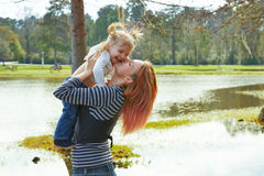 Mother playing throwing up baby girl in a lake Royalty Free Stock Photos