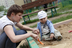 Mother playing with toddler. Mother playing with her toddler in sandbox Royalty Free Stock Photos
