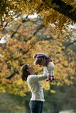 Mother playing with toddler under tree Stock Image