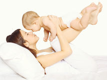 Mother playing together with baby on the bed Stock Photos
