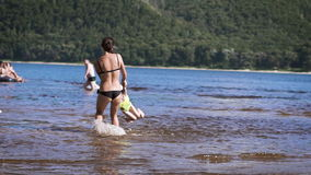 Mother playing turning around her baby girl daughter in the lake stock footage