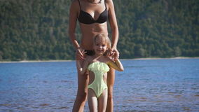 Mother playing turning around her baby girl daughter in the lake stock video footage