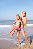 Mother playing with young girl on beach Stock Photography