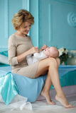 Mother plays with the baby,putting him on her knees Royalty Free Stock Images