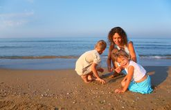 Mother plays with children finding shells on sand Royalty Free Stock Photo