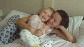 Mother plays with daughter on the bed stock video