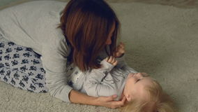 Mother plays with daughter on the floor stock video