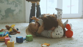 Mother plays with daughter on the floor stock footage
