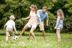 Mother plays football soccer with family. In summer royalty free stock photography