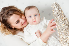 Mother plays with her baby daughter. Portrait on starry wallpaper Stock Photos