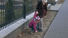 Mother plays with her daughter, girl jumps from the fence. The concept of the family. Slow motion stock footage