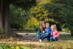 Mother plays with her daughter and son in the park by the pond stock photo
