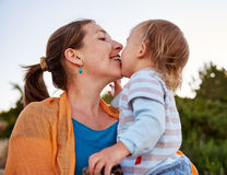 Mother plays with her little baby child outdoors Stock Photos