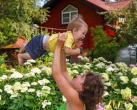Mother plays with her little baby outdoors. Lifting him high above head Royalty Free Stock Photography