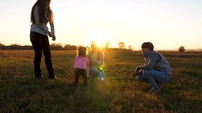 Mother plays with her little daughter ball on field in rays of yellow sun. Slow motion. happy family and children stock video footage