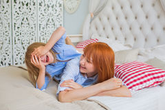 Mother plays with her little daughter on a bed - closes eyes Stock Photography