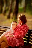 Mother plays with her little son on the bench stock photo