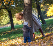 Mother plays with her little son in the park. In early autumn Royalty Free Stock Image