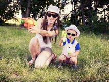 Mother plays with her son outdoors Stock Photos