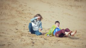 The mother plays with her son in a raincoat and runs down the sea at the beach. 4k stock video footage