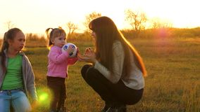 Mother plays with little daughter in ball. Slow motion. happy child runs with ball on grass. Family playing with small stock footage