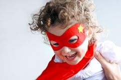 Mother plays with little superhero child girl Stock Image