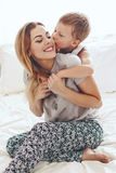 Mother plays with son in bed. Young mother with her 6 years old little son dressed in pajamas are relaxing and playing in the bed at the weekend together, lazy Stock Photos