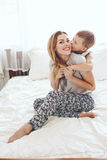 Mother plays with son in bed Stock Photography