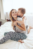Mother plays with son in bed. Young mother with her 6 years old little son dressed in pajamas are relaxing and playing in the bed at the weekend together, lazy Stock Photography