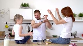 Mother plays with the son during a breakfast. On this video you can see as parents have breakfast with the son and play in parallel. Mother plays with the son so stock footage