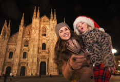 Mother pointing in camera and daughter in Santa Hat, Milan Royalty Free Stock Photos