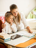 Mother pointing in exercise book and explaining homework to daug Royalty Free Stock Images