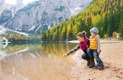 Mother pointing and kneeling next to daughter at Lake Bries Royalty Free Stock Photography