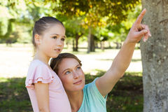Mother pointing at something besides daughter at park Royalty Free Stock Image