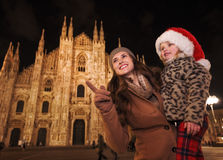 Mother pointing on something to daughter in Santa Hat, Milan. Family Christmas holidays in style. Happy mother pointing on something to daughter in Santa Hat in Royalty Free Stock Photography