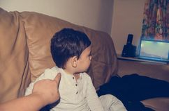 Mother poking toddler for attention as hi is to busy watching cartoons. Selective focus stock photos