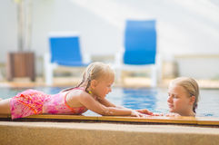 Mother in pool and daughter on pool side have fun and talk in tr Stock Image