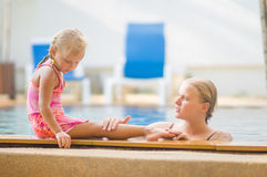 Mother in pool and daughter on pool side have fun and talk in tr Stock Photography