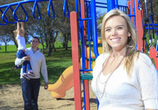 A mother portrait and boyfriend and children play. On the playgroundg Stock Photography