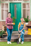 Mother with potted plant and daughter with garden shovel looking at camera royalty free stock photos