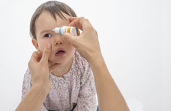 Mother pouring eye drops in the eye of her daughter Stock Images