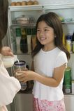Mother Pouring Milk For Daughter in kitchen by open fridge close up of daughter Stockfoto