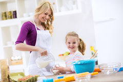Mother pouring milk to child Stock Images